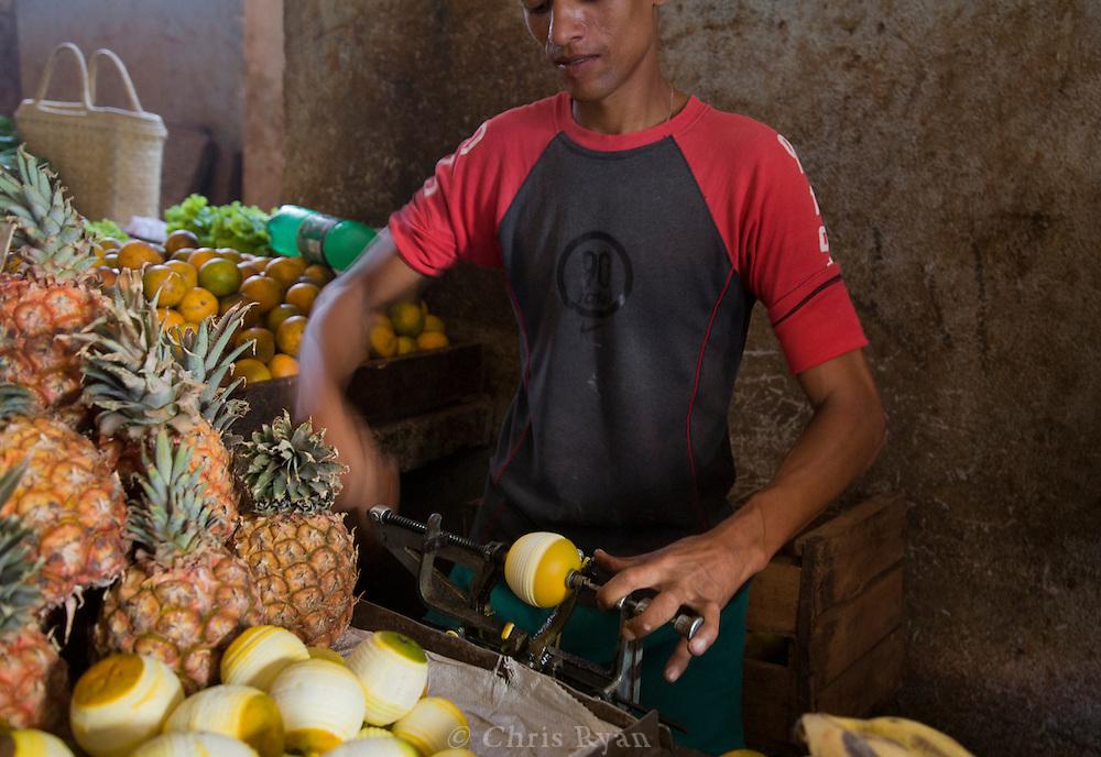 Man preparing produce to sell, Mercado Agropecuario Cuatros Caminos, Havana, Cuba
