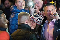 © Licensed to London News Pictures . 01/01/2017 . Manchester , UK . Marriage proposal in the crowd - pictured wife to be MALENA THIBEAULT (20) and her fiance JORDAN CATTON (22), kissing after she accepts . Thousands gather as Manchester celebrates the start of 2017 , with a fireworks display in front of the Town Hall in Albert Square . Photo credit : Joel Goodman/LNP