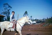 Young boy riding a horse along the street of Laranjeiras do Sol, Paraná state, Brazil in 1962