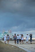 Group of friends walking on road under storm cloud, Havana, Cuba