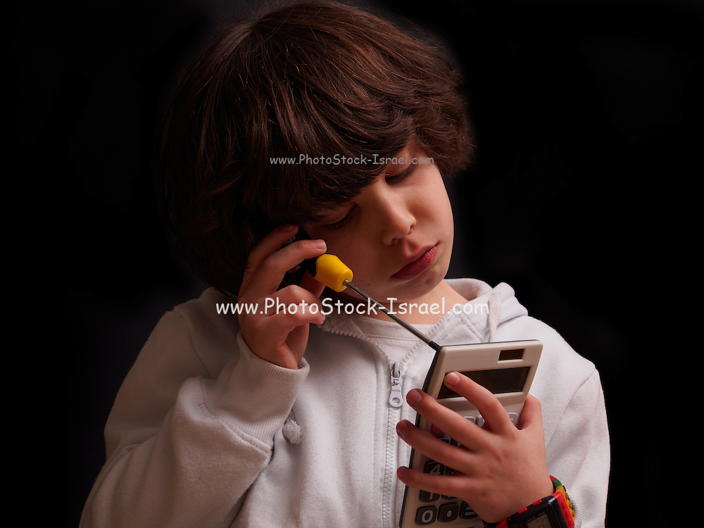 young boy with screw driver dismantling a calculator