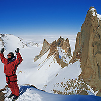 Rick Ridgeway warms himself in morning sun while climbing a  satellite peak of the Troll's Castle, Filchner Mountains, Queen Maud Land, Antarctica.