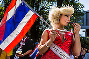 "15 JANUARY 2014 - BANGKOK, THAILAND:  A transvestite supporter of anti-government protest leader Suthep Thaugsuban waits to giver money to Suthep during a protest march in Bangkok. Tens of thousands of Thai anti-government protestors continued to block the streets of Bangkok Wednesday to shut down the Thai capitol. The protest, ""Shutdown Bangkok,"" is expected to last at least a week. Shutdown Bangkok is organized by People's Democratic Reform Committee (PRDC). It's a continuation of protests that started in early November. There have been shootings almost every night at different protests sites around Bangkok. The malls in Bangkok are still open but many other businesses are closed and mass transit is swamped with both protestors and people who had to use mass transit because the roads were blocked.   PHOTO BY JACK KURTZ"