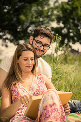 Woman with her husband and reading book on meadow in the countryside, Bavaria, Germany