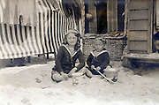two children playing in the sand in front of their beach cottage 1920s