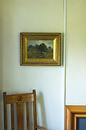 House room interior with old furniture including a landscape painting a chair and fire place surround