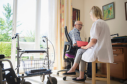 Nurse discussing with senior man in rest home, Bavaria, Germany, Europe