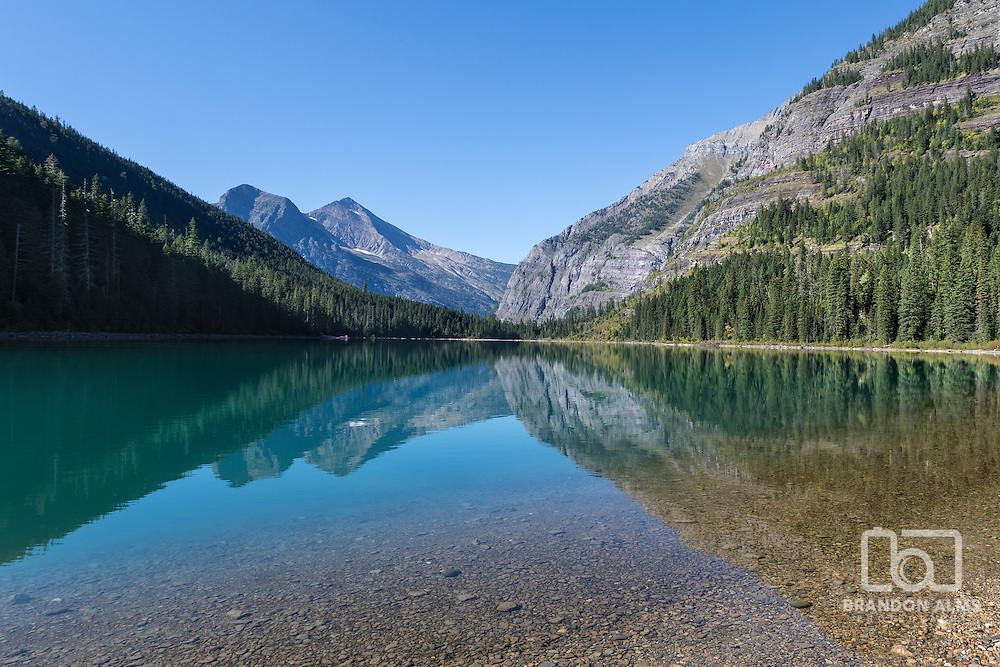 Beautiful mountains and trees reflecting into Avalanche Lake in Glacier National Park Montana.