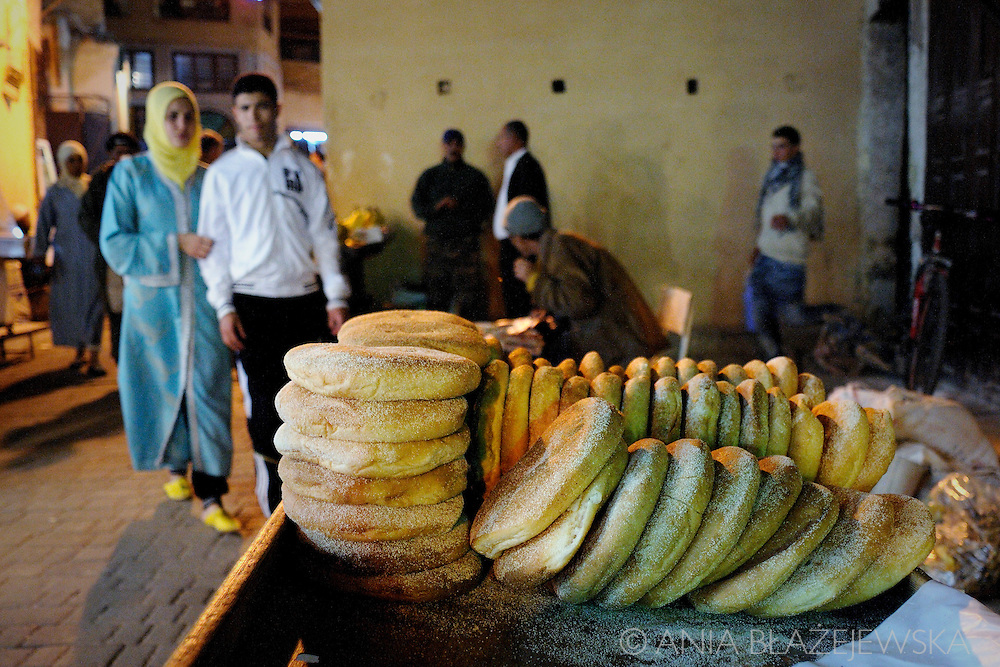 Morocco, Fez. Couple passing the stall with bread in the street of the medina in Fez.