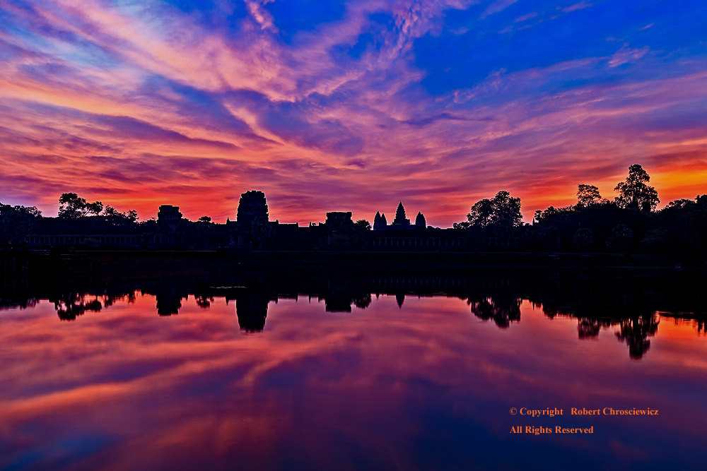 Mirror Image at Angkor Wat: A stunning sunrise, over the silhouetted ancient Khmer ruins at Angkor Wat, is reflected the surrounding moat, Siem Reap Cambodia.