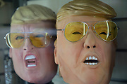 Donald Trump masks wearing yellow sunglasses in a shop window in London, England, United Kingdom.