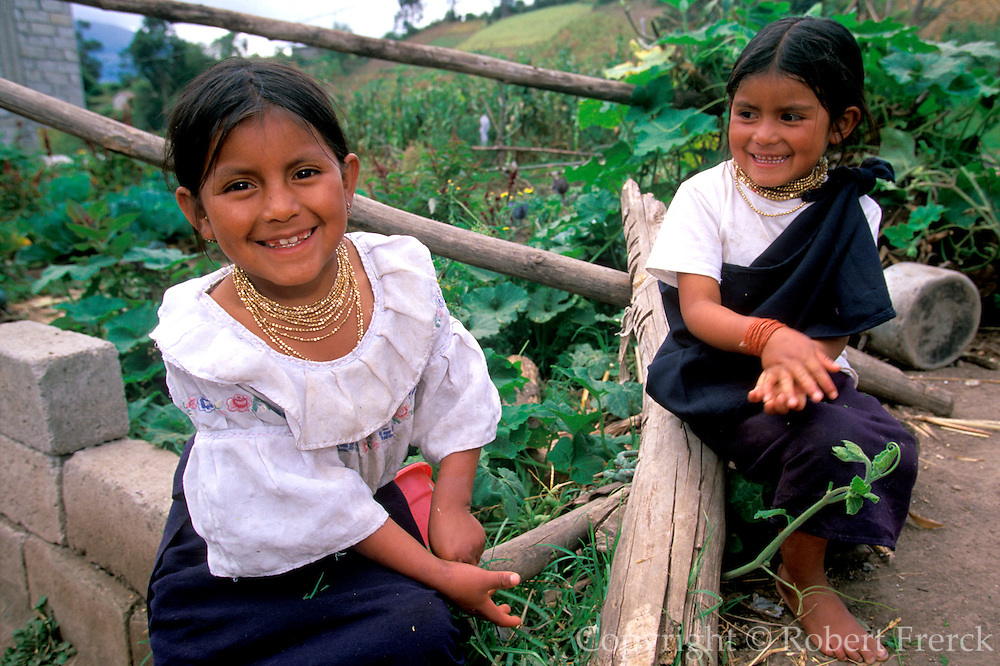 ECUADOR, HIGHLANDS young sisters in trad. Otavalo dress