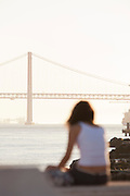 A girl sits at Praca do Comercio, Commercial Square, a popular meeting point. Seen at sunset by Ponte 25 de Abril, the 25th of April Bridge, which crosses the Tagus River in Lisbon, Portugal