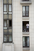 woman staring out from his balcony to the street Paris France