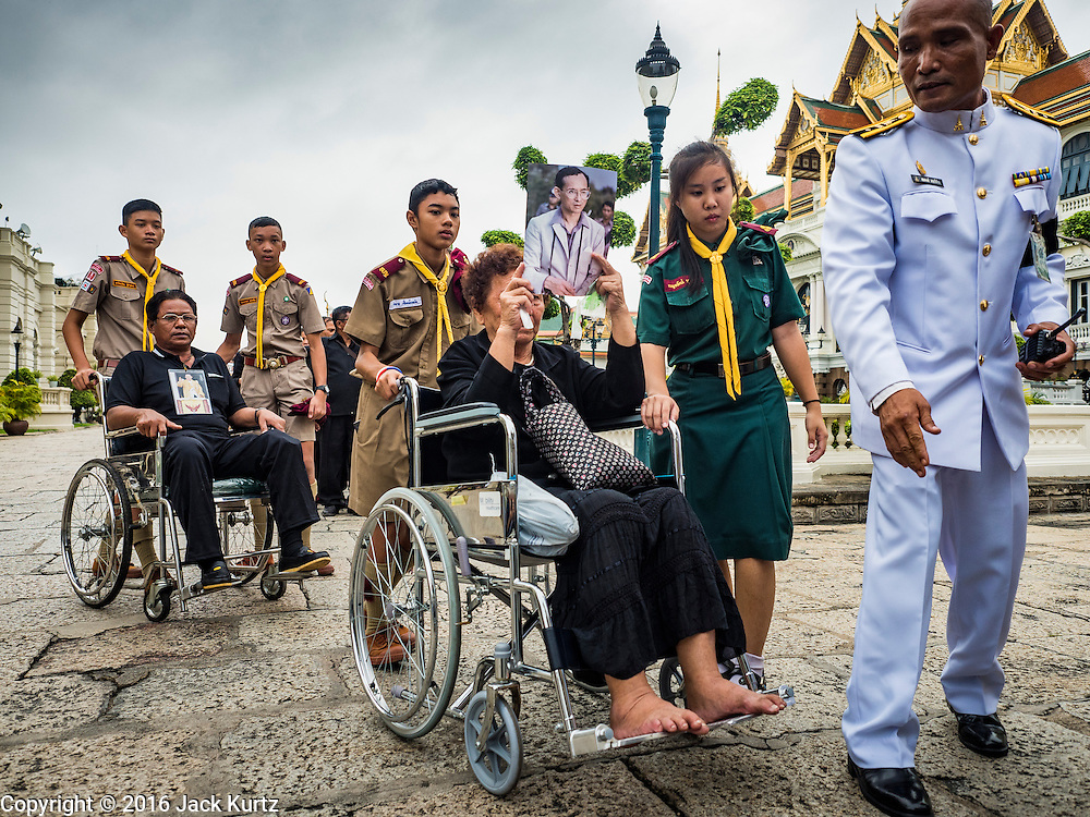 29 OCTOBER 2016 - BANGKOK, THAILAND: A Thai boy scout helps a woman in a wheelchair go into the Grand Palace to pay homage to the late Thai King. Saturday was the first day Thais could pay homage to the funeral urn of the late Bhumibol Adulyadej, King of Thailand, at Dusit Maha Prasart Throne Hall in the Grand Palace. The Palace said 10,000 people per day would be issued free tickerts to enter the Throne Hall but by late Saturday morning more than 100,000 people were in line and the palace scrapped plans to require mourners to get the free tickets. Traditionally, Thai Kings lay in state in their urns, but King Bhumibol Adulyadej is breaking with tradition. His urn reportedly contains some of his hair, but the King is in a coffin,  not in the urn. The laying in state will continue until at least January 2017 but may be extended.       PHOTO BY JACK KURTZ