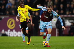 Watford's Abdoulaye Doucoure (left) and Burnley's Chris Wood battle for the ball during the Premier League match at Turf Moor, Burnley.