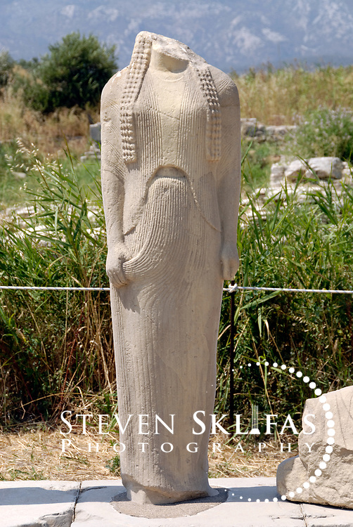 Iraion. Samos. Greece. View of one statue from the copy of the statue group by the great 6th century sculptor Genelos. Dating from 560 - 550 B.C, the steeped pedestal originally contained 6 statues of which four have survived. The statues are representing a father, mother and children are of a distinguished family of the time.  Each of the figures has an inscription stating its name. The work displays interesting innovations that influenced the art of Ionia.