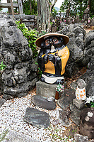Tanuki Badger at Zenzibuji Temple, Temple Number 32 - Zenzibuji temple is near Chikurinji temple on a hill facing Tosa Bay.  Zenzibu-ji is Temple number 32 on the Shikoku Pilgrimage Trail. Kobo Daishi visited this temple in 807 and trained here. Daishi wished for thesafety of ships in Tosa Bay. Inside the temple is a statue of Kannon the Goddess of Mercy. Tanuki is the Japanese word for a raccoon.  These creatures have been represented in Japanese folklore for hundreds of years.  The tanuki have a reputation for being mischievous.  At the same time they are jolly, good at disguising themselves. They are also absent-minded. and gullible according to legend