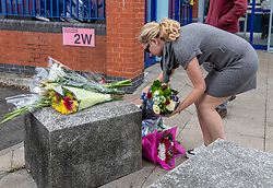 © Licensed to London News Pictures. 25/09/2020. London, UK. A police officer lays flowers outside Croydon Police Station in South London where a custody sergeant was shot dead inside the station last night. The Shooter who turned the gun on himself has survived and was taken to hospital in critical condition. Photo credit: Alex Lentati/LNP