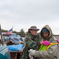 Kirk Mitchell, 49, and Pete Tsinnijinnie, the Chinle veteran group commander, change over duties with the flag along AZ-264, during the Veterans Walk to the Navajo Nation Council Chambers in Window Rock on Wednesday.