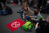 DEU, Deutschland, Germany, Berlin, 09.10.2019: Kundgebung der Aktivisten von Extinction Rebellion (XR) mit einer Strassenblockade auf dem Kurfürstendamm (Kudamm). Die Umweltschützer wollen mit zahlreichen Aktionen und Blockaden in der Stadt auf ihr Anliegen einer strengeren Klimapolitik aufmerksam machen. Eine Fahne mit dem Logo der XR-Bewegung, einer Sanduhr in einem Kreis, liegt auf der Strasse.