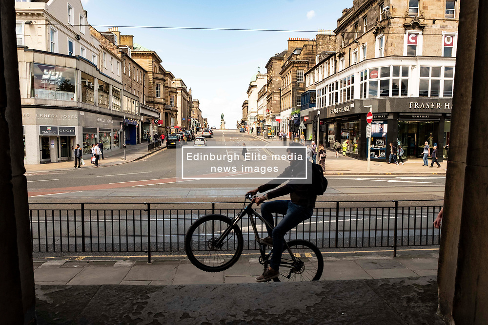 Pictured: At least one cyclist was enjoying the lack of footfall on the main shopping street in Edinburgh<br /> <br /> Princes Street in Edinburgh has been hit hard by the Covid19 lockdown and the locals are taking time to get used to new freedoms. Queues outside fast food outlets are, sadly, no surprise.