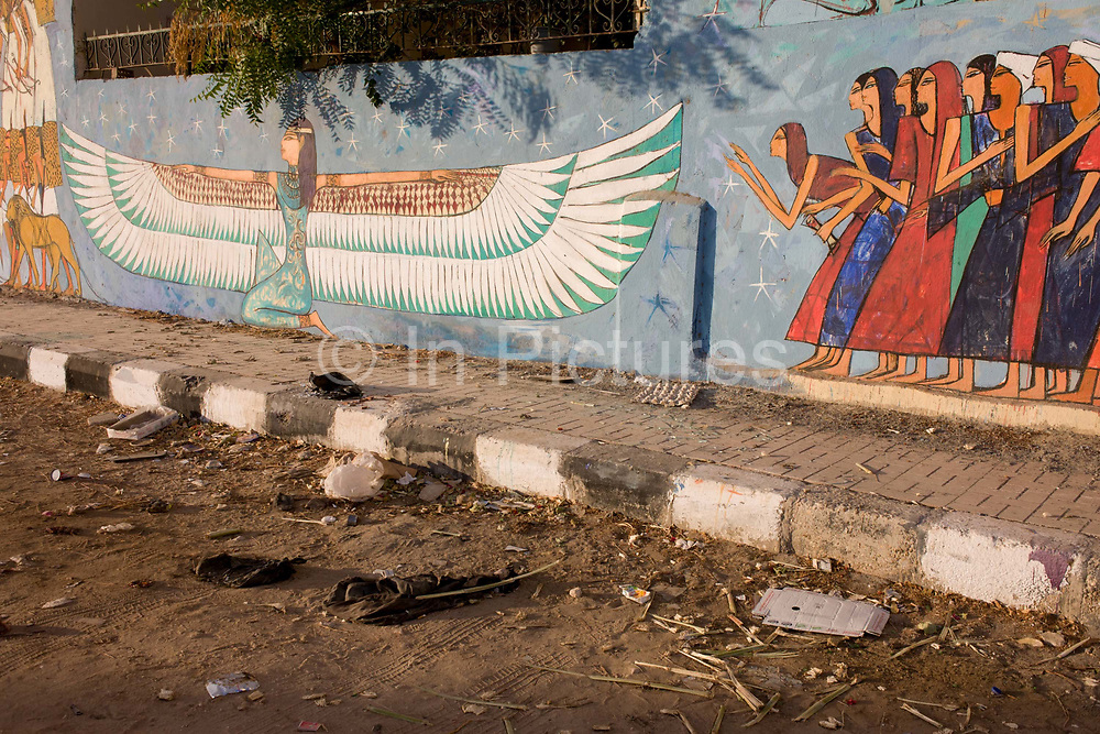 Modern hieroglyphic artwork painted on a wall of local wasteground in the village of Gezirat on the West Bank of Luxor, Nile Valley, Egypt. Shown on the wall is an unknown queen (possibly Queen Hatshepsut, the 5th Pharaoh of the 18th dynasty) being courted by the people.