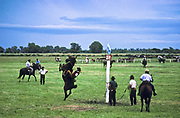 Gauchos at a horse breaking competition (known as a Jineteada) on a ranch, similar to bronco bucking. Lincoln, Buenos Aires, Argentina.