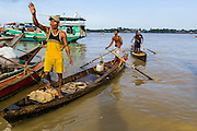 17 JUNE 2013 - YANGON, MYANMAR:  A man in a canoe lands in a large Yangon fish market. The market serves both domestic retail customers and wholesale international customers. With thousands of miles of riverine waterways and ocean coastline Myanmar has a large seafood and fishing industry.     PHOTO BY JACK KURTZ
