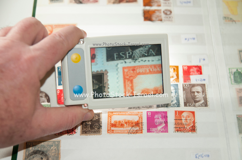 A vision impaired stamp collector uses a handheld electronic magnifier to inspect a stamp in his stamp collection