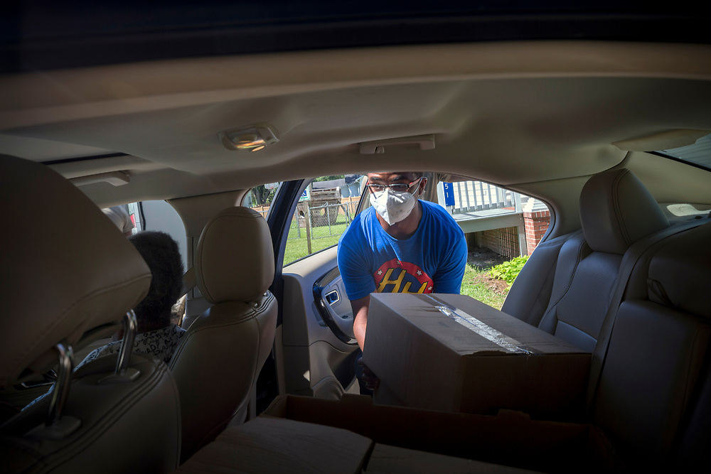 SUMMERTOWN, GA - JULY 14, 2020: A volunteer with the Summertown Food Pantry places a box of food into the back seat of a car. Members of the food drive practice social distancing by placing boxes in the trunk or back seat. (AJC Photo/Stephen B. Morton)