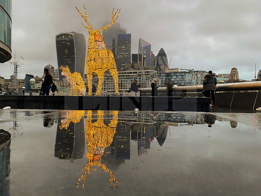 © Licensed to London News Pictures. 13/12/2020. London, UK. Reflection of London's financial district and reindeers Christmas decoration on a wet surface caused by rainfall in the capital. Photo credit: Dinendra Haria/LNP