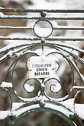Attention Chien bizarre sign on gate in snow