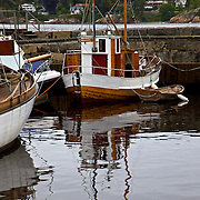 Boats and their reflections in water along the Numedalslågen River in the harbor town of Larvik, Norway