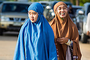 28 JULY 2014 - KHLONG HAE, SONGKHLA, THAILAND: Women walk into Eid al-Fitr services at Songkhla Central Mosque in Songkhla province of Thailand. Eid al-Fitr is also called Feast of Breaking the Fast, the Sugar Feast, Bayram (Bajram), the Sweet Festival and the Lesser Eid, is an important Muslim holiday that marks the end of Ramadan, the Islamic holy month of fasting.   PHOTO BY JACK KURTZ