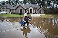 Covington Louisiana, March, 12, 2016,  Man helps a pet and a baby to safety carrying them out of the floodwaters in the Tallow Creek subdivision. 14 inches of rain fell in less than 24 hours, after three days of intermittent rain, causing flash floods. The Tchefuncte River  and Bogue Falaya River<br />  crested on Saturday morning but the flood event continued into the night for those in Tallow Creek.