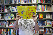 A man holds a copy of the children's book, Horrid Henry's Big Bad Book in front his face. He is standing in front of a bookshelf full of books. HMP Kingston, Portsmouth, United Kingdom. As part of the Storybook Dads Program a prisoner reads a story for his 8-year-old son. HMP Kingston.