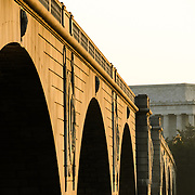 The structure of Memorial Bridge crossing the Potomac catches the early morning light, with the Lincoln Memorial in the distance on the other side of the river.