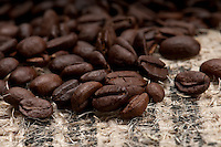 Macro shot of coffee beans over burlap.