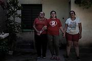 """Maricel (30) junto a su madre y una de sus hermanas. La situación discapacitante que se generó debido al incumplimiento del Estado y las obras sociales en la Rioja, hizo que todas las mujeres de la familia se uniesen y formaran una especie de tribu para darle apoyo continuo a Maricel y ayudarla en el cuidado de Renata y los trámites infinitos en la Ciudad. Su abuela, sus tías y sus primas también son """"Cuidadoras"""". Aun así, Maricel no puede dormir de noche, se despierta rogando que no haya cortes en el suministro eléctrico del pueblo, luego besa a Renata mientras le limpia la cánula endotraqueal que utiliza para poder respirar y controla el funcionamiento de los aparatos que le dan oxígeno."""