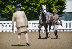 © Licensed to London News Pictures. 10/05/2017. Windsor, UK. Confirmation judge Miss M L Hennessy (L) watches as a rider runs with her horse in the Small Hunter competition category on the first day of the Royal Windsor Horse Show. The five day equestrian event takes place in the grounds of Windsor Castle. Photo credit: Peter Macdiarmid/LNP