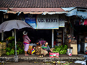 03 AUGUST 2017 - SUKAWATI, BALI, INDONESIA: A woman makes a daily Hindu offering in front of her shop in the local market in Sukawati, Bali. Bali's local markets are open on an every three day rotating schedule because venders travel from town to town. Before modern refrigeration and convenience stores became common place on Bali, markets were thriving community gatherings. Fewer people shop at markets now as more and more consumers go to convenience stores and more families have refrigerators.     PHOTO BY JACK KURTZ