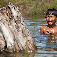 Boy swimming in a puddle along a ricefield located somewhere between Siem Reap and the road leading to the Beng Mealea temple.