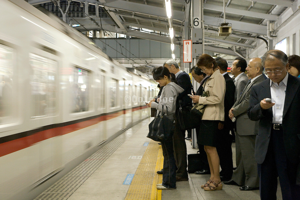 commuters waiting in line for their train Japan Tokyo