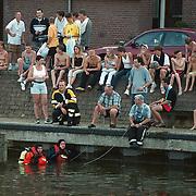 Gestolen auto, Opel Corsa, gevonden in de aanloophaven Huizen, duikers van de brandweer bergen het wrak onder publieke belangstelling