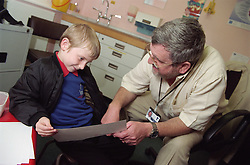 Professor in community paediatric health centre discussing picture drawn by young patient,