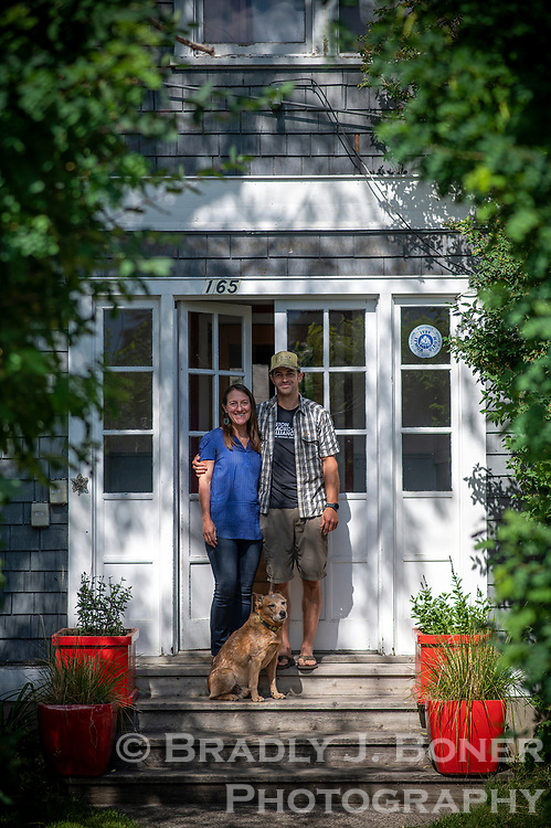 Brigid Mander and her boyfriend Alex Jakovac with their pup, Curley, outside one of the old St. John's Hospital nurses quarters on Glenwood Street. Mander, who has lived in an upstairs unit for more than six years, has spearheaded an effort to save the two structures from demolition.