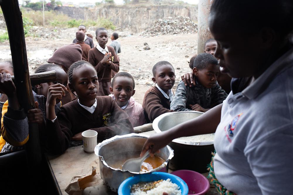 School children wait for their lunch at a street stall in Nairobi, Kenya