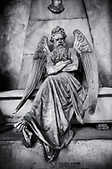 Heavens Gate - Black and white art photo of the stone sculpture of an angel sitting on a sarcophagus. Piaggio Tomb sculpted by S Saccomanno 1876. Section A, no 46, The  monumental tombs of the Staglieno Monumental Cemetery, Genoa, Italy .<br /> <br /> Visit our PEOPLE & PLACES PHOTO ART COLLECTIONS for more photos to buy as buy as wall art prints https://www.photoshelter.com/mem/images/index#/C00001WetsxVxNTo/ .<br /> <br /> Visit our LANDSCAPE PHOTO ART PRINT COLLECTIONS for more wall art photos to browse https://funkystock.photoshelter.com/gallery-collection/Places-Landscape-Photo-art-Prints-by-Photographer-Paul-Williams/C00001WetsxVxNTo