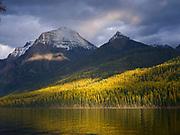 Breaking storm sunlight illuminating fall vegetation above Bowman Lake with Square Peak and Cerulean Ridge beyond, Glacier National Park, Montana.